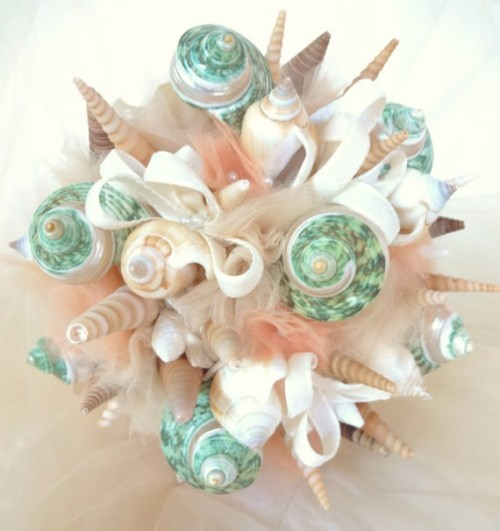 a unique beach wedding bouquet of neutral tulle, seashells of bright tones is a gorgeous option for a beach bride