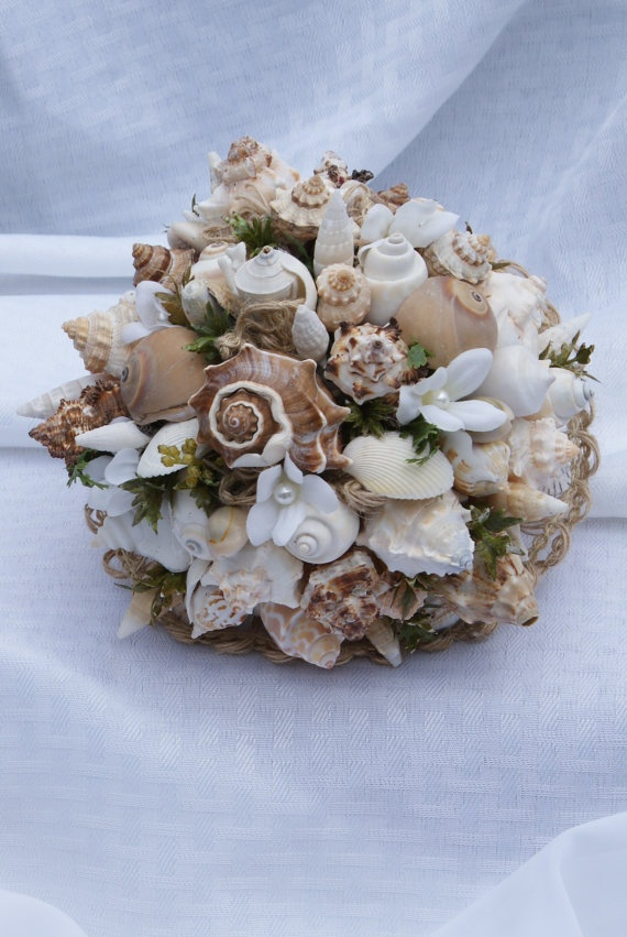 a rough wedding bouquet of seashells, pearls, greenery, white fabric blooms shaped as a ball