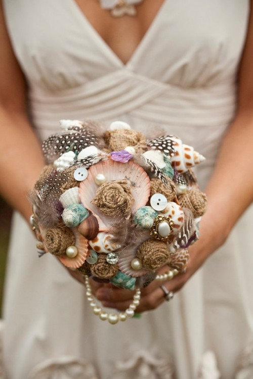 a bright and non-typical wedding bouquet composed of buttons, pearls, seashells and feathers
