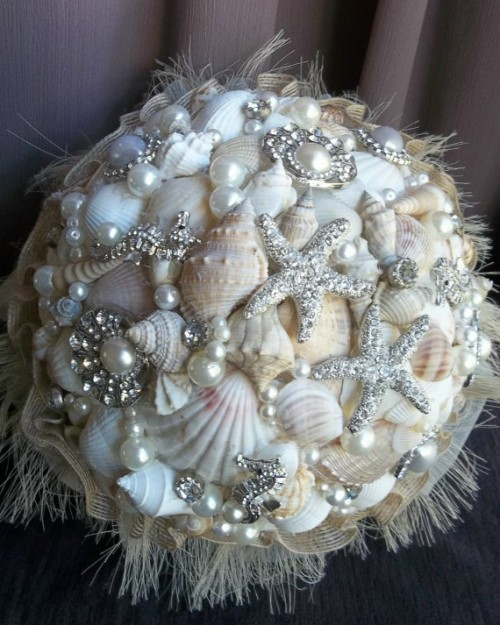 a sparkling beach wedding bouquet of neutral seashells, pearls and starfish brooches plus a fringe wrap