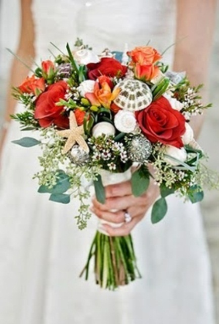 a bold coral wedding bouquet spruced up with neutral and white seashells plus greenery
