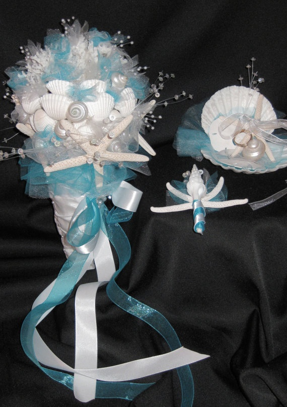 a blue and white wedding bouquet made of seashells, beads and farbic flowers plus ribbons