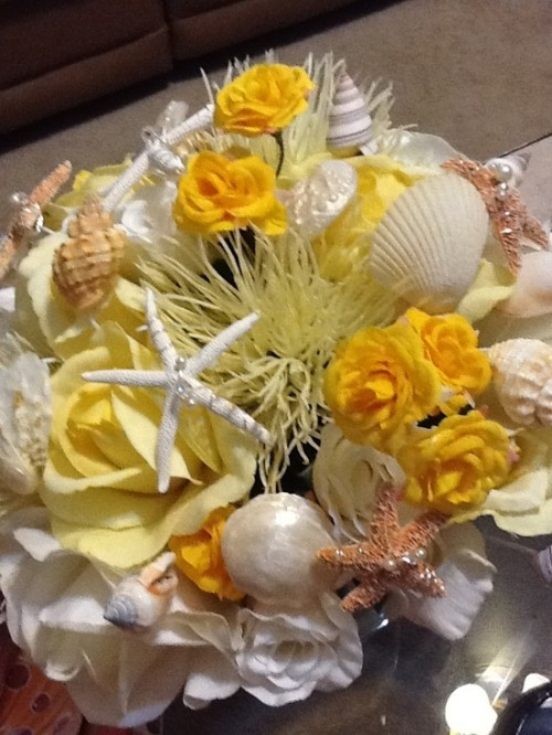 a bold beach wedding bouquet composed of white and yellow blooms, seashells and starfish