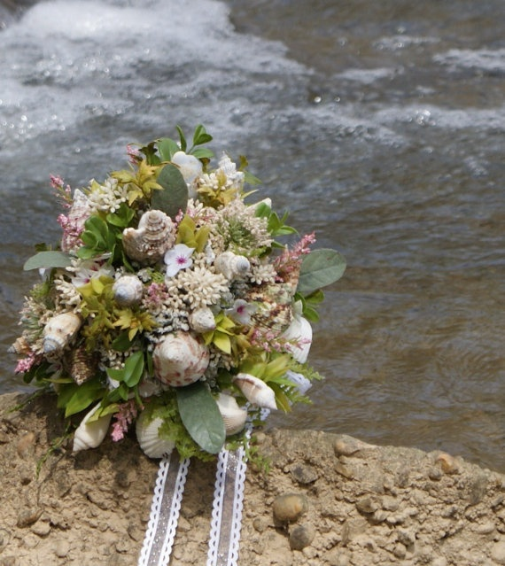 a simple beach wedding bouquet with white blooms, greenery and some seashells plus white ribbons