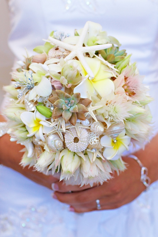 a neutral beach wedding bouquet dotted with pastel blooms, succulents, seashells and sea urchins plus some greenery