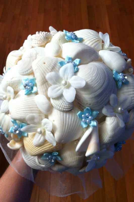 a beach wedding bouquet with seashells, white and blue fabric flowers, pearls and beads