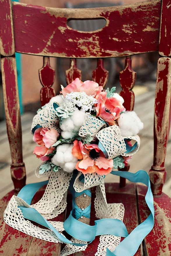 a bouquet of bright coral blooms, cotton, blue and lace ribbons for a bright beach wedding
