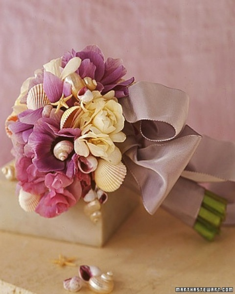 a pink and neutral wedding bouquet with seashells and a dusty pink ribbon for wrapping the bouquet