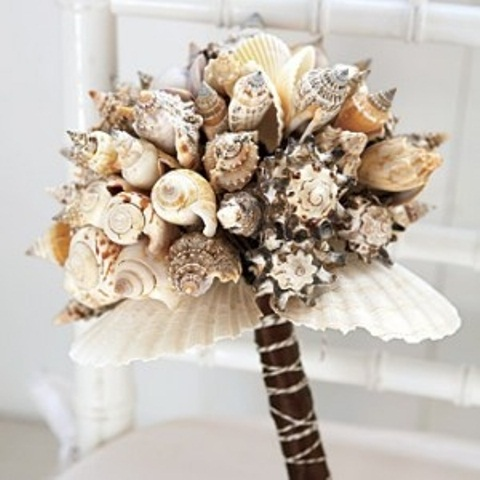 a beach wedding bouquet of dark and neutral seashells and a dark wrap is a pretty idea for a beach wedding