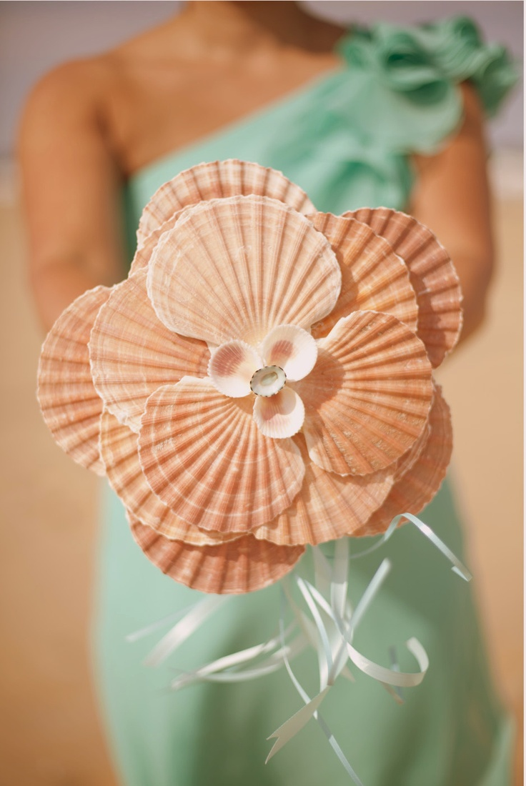 a unique beach wedding bouquet made of large seashells and some thin ribbons