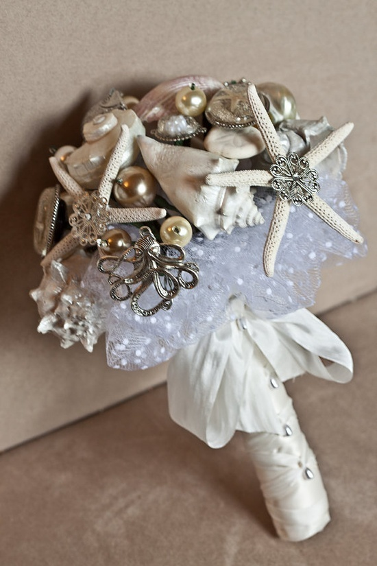 a quirky beach wedding bouquet of seashells, sea inspired brooches, starfish and pearls plus a sequin wrap