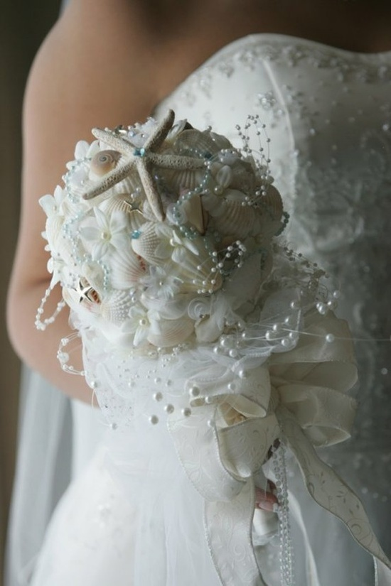a white beach wedding bouquet of seashells, starfish, pearls and fabric flowers all over