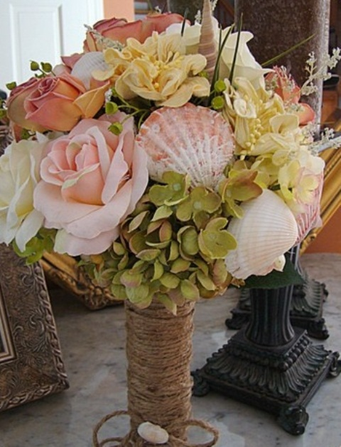 a beach wedding bouquet of neutral and pink blooms, greenery and pink seashells looks very natural