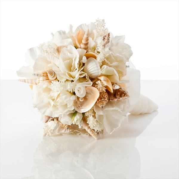 a chic neutral wedding bouquet of blooms, seashells and coral looks very cool and elegant