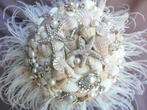 a white beach wedding bouquet of neutral shells, sparkling starfish brooches, pearls and feathers