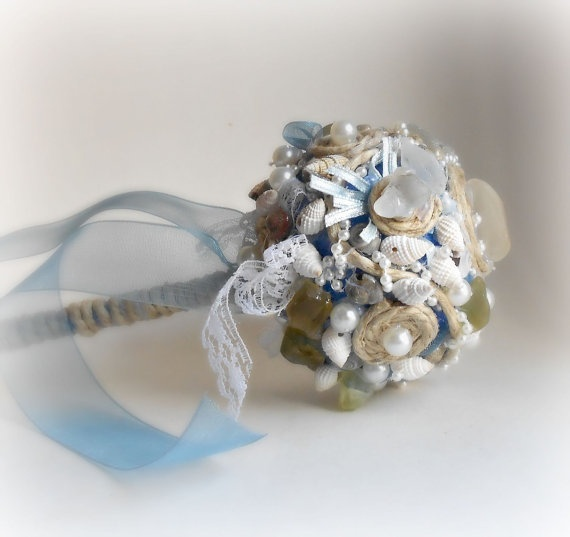 a quirky wedding bouquet with shells, pearls, neutral pebbles and ribbons for decor