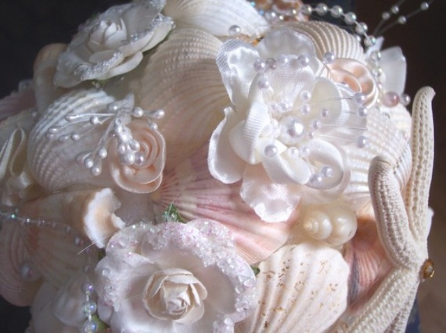 a pastel and white beach wedding bouquet of pink seashells, white seashells, pearls and fabric blooms