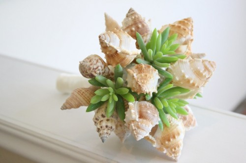 a unique beach wedding bouquet of neutral shells and succulents looks very unusual