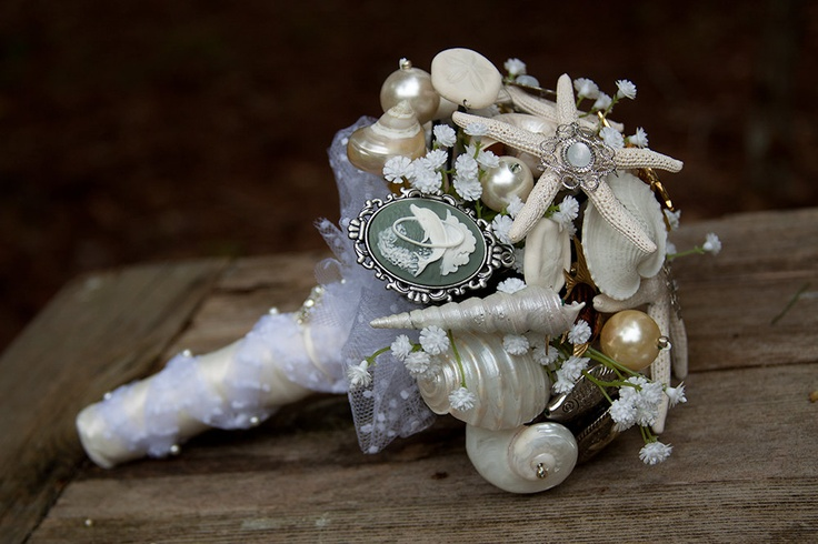 a neutrla beach wedding bouquet composed of brooches, pearls, baby's breath and ribbons