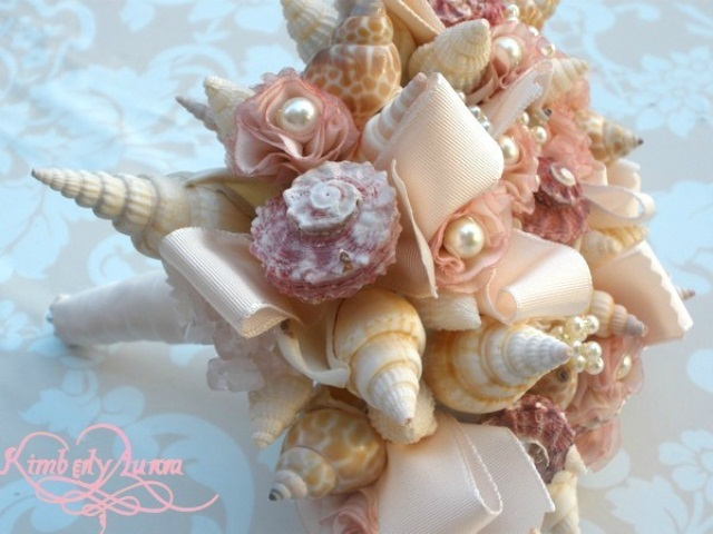 a neutral beach wedding bouquet made of seashells, neutral ribbons and fabric blooms
