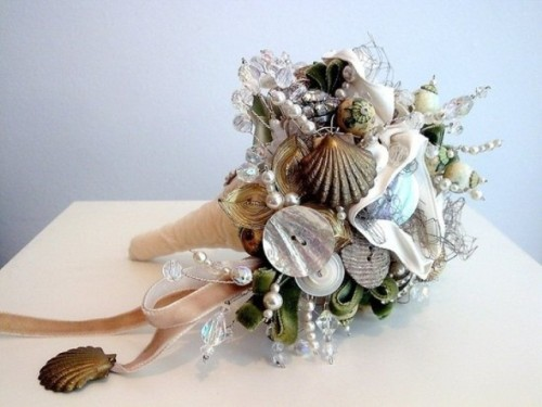 a beach wedding bouquet of seashells, beads and pearls, greenery and pink ribbons