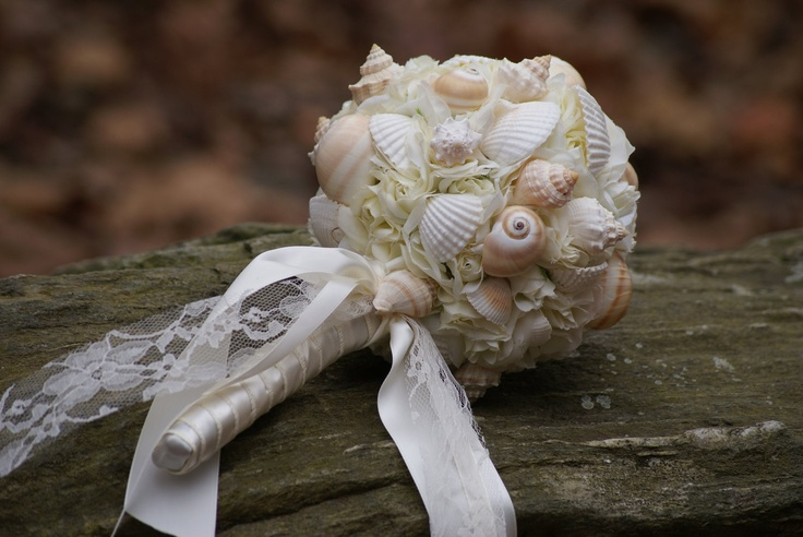 a blush and white ball wedding bouquet fully made of seashells