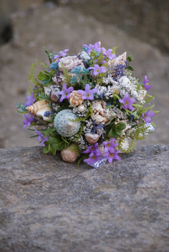 a bright beach wedding bouquet with purple and blue blooms, greenery and neutral and blue shells