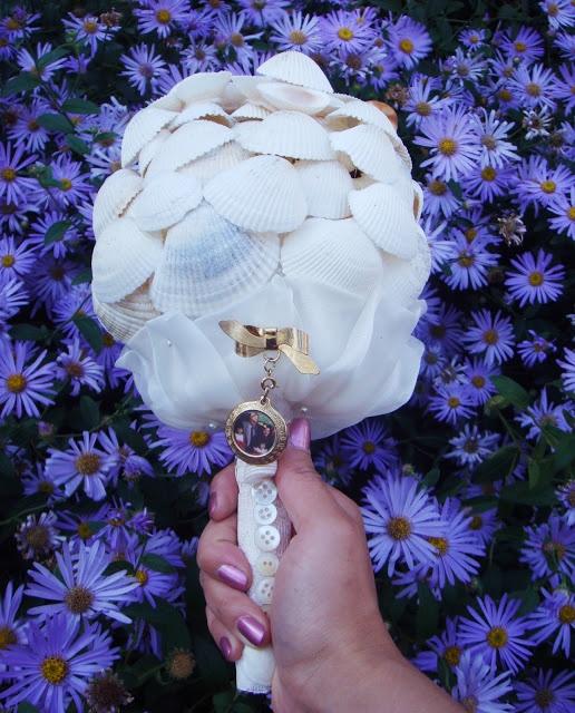 a white wedding bouquet made of seashells, white ribbon and a single photo pendant