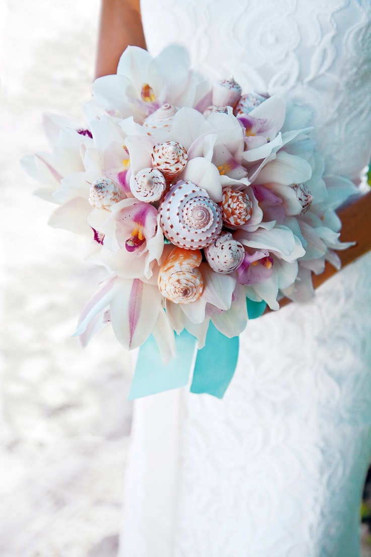 a beautiful white orchid wedding bouquet with some seashells incorporated and bright ribbons
