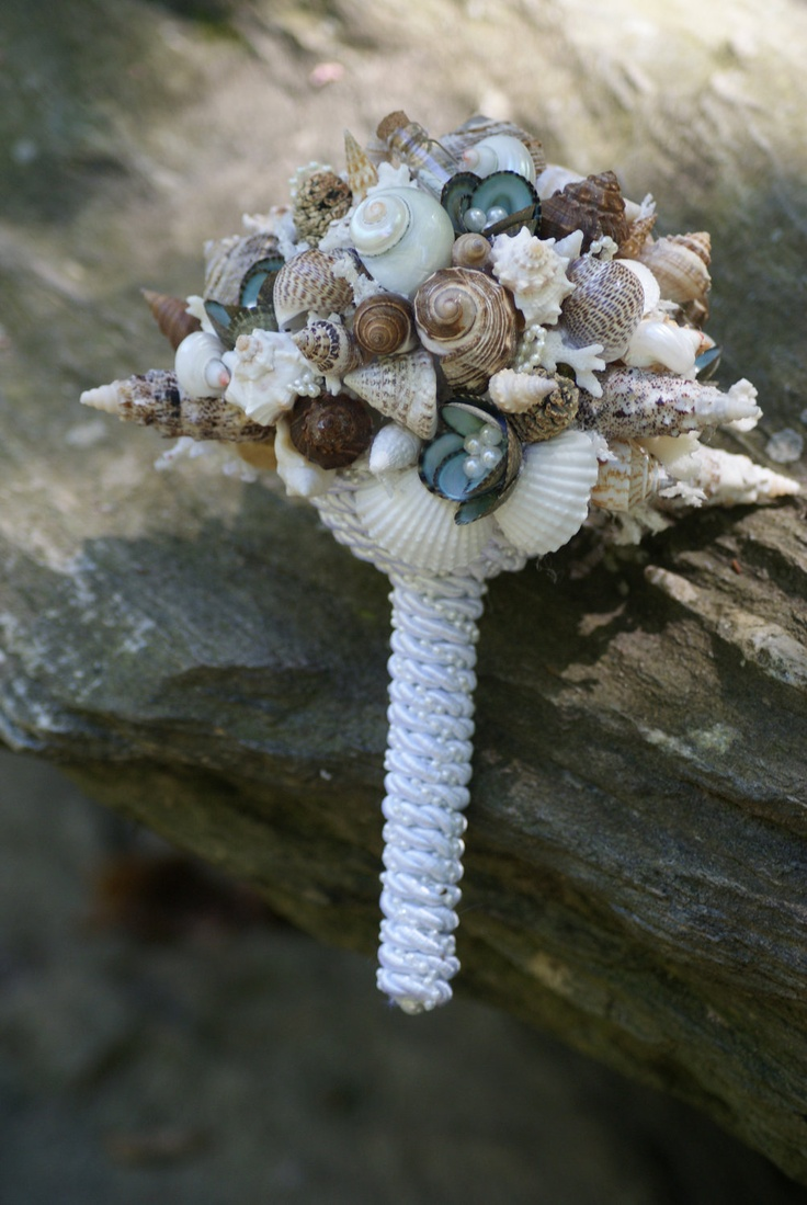 a chic beach wedding bouquet of neutral, green and brown seashells, pearls and rope wrap
