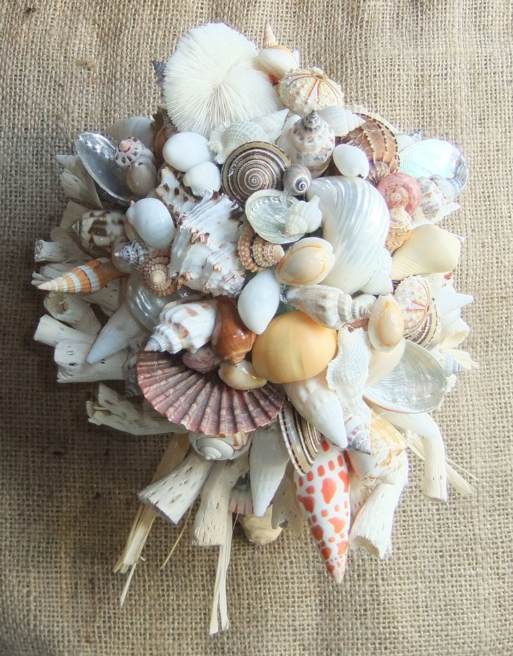 a neutral beach wedding bouquet of seashells, starfish and other sea inspired stuff
