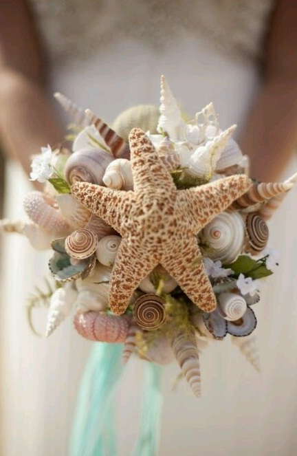 a unique beach wedding bouquet of seashells, sea urchins and star fish, some white blooms nd greenery