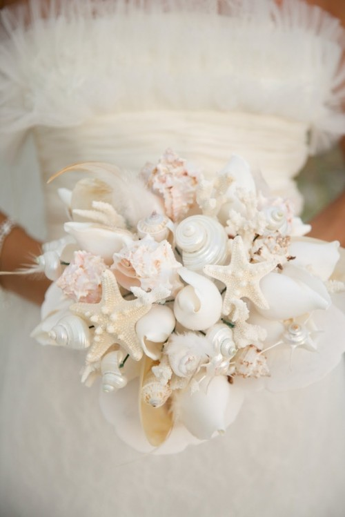 a white beach wedding bouquet made of seashells, feathers and starfish