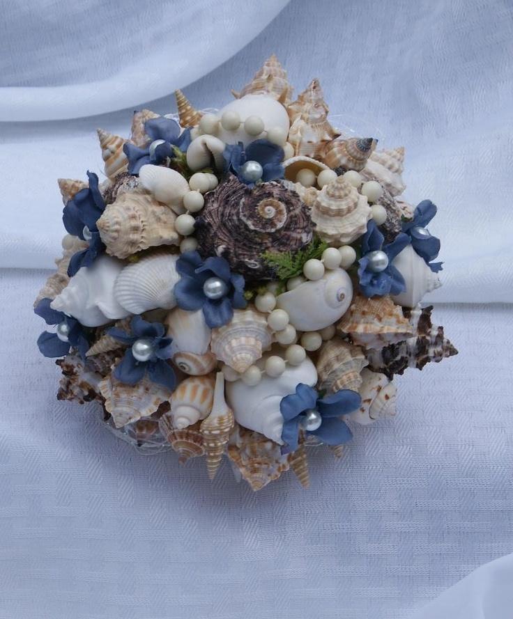 a fun beach wedding bouquet made of seashells, pearls, beads, blue fabric blooms looks unusual