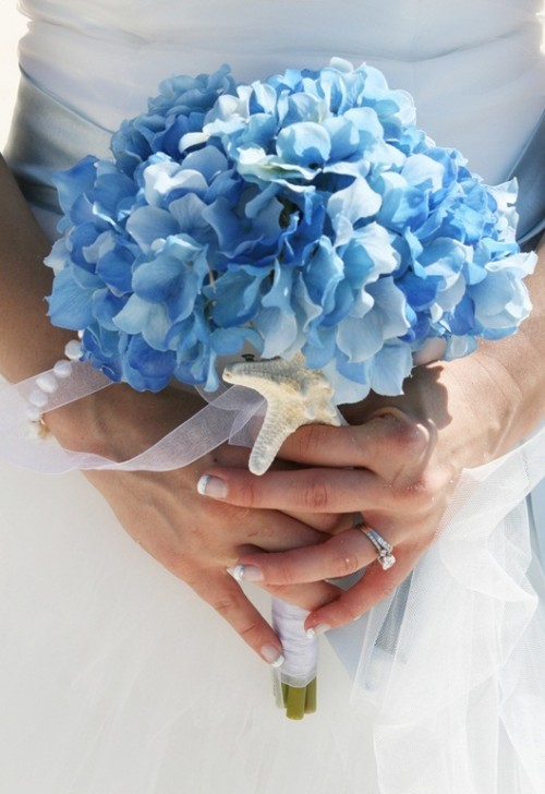 a beach wedding bouquet of blue hydrangeas and a single starfish as an accent