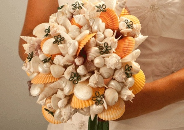 a beach wedding bouquet of yellow, neutral and mother of pearl shells plus fabric flowers