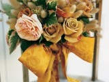 a bright warm-colored wedding bouquet of yellow and blush blooms, large leaves and bunny tails plus a gold yellow printed ribbon bow is cool for a pretty and bold rustic wedding