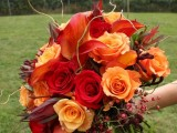 a colorful fall wedding bouquet of orange, red and burgundy blooms, berries, greenery and twigs is a very catchy and bold idea