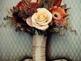 a bold fall boho wedding bouquet of rust, burgundy and neutral blooms, feathers and dark foliage, gilded greenery plus a tan wrap