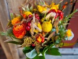 a bright wedding bouquet of orange and yellow blooms, billy balls, cranberries and wheat and greenery is a very cool idea for a rustic fall bride