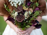 a bold and contrasting fall wedding bouquet of deep purple callas, white blooms, greenery and feathers and lotus slices is a cool idea for a moody fall wedding