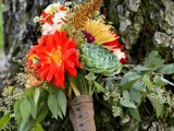 a bold fall wedding bouquet of orange, red, yellow and white blooms, greenery, grasses and a succulent plus a burlap wrap on buttons is a gorgeous idea for a colorful fall rustic wedding