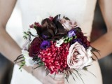 a small contrasting wedding bouquet of burgundy, black, purple and light pink blooms and greenery is a bold color statement for a colorful or moody fall wedding