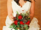 a colorful fall wedding bouquet of lots of greenery, hot red blooms, berries and some dark foliage is a veyr pretty idea for a boho bride