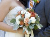 a creative fall wedding bouquet of white peonies, blush peony roses and rust pincushion proteas plus greenery is a gorgeous idea for the fall