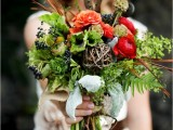 a colorful and textural fall wedding bouquet of greenery, orange and depe red blooms, a vine ball, privet berries, feathers and lotus is a catchy idea for a fall woodland bride