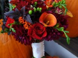 a sumptuous fall wedding bouquet of burgundy, deep purple, orange, red blooms, berries and dark foliage for a bright rustic wedding in the fall