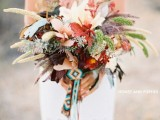 a lush dimensional fall wedding bouquet with greenery, feathers, foliage and bright blooms plus a colorful boho wrap and ribbons is a cool idea for a boho fall bride