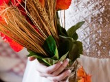 a catchy and colroful wedding bouquet of deep red and orange blooms, wheat and some greenery, a yarn wrap and some faux fall leaves is a cool idea for a rustic bride