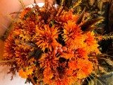 a colorful and dimensional fall wedding bouquet of orange blooms, berries and feathers plus greenery is a cool idea for a fall wedding